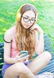 Un teenger hermoso escucha la música se sienta en el banco Imagen de archivo libre de regalías
