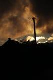 Un tejado de la casa del campo y una línea eléctrica en el tiempo de la puesta del sol imágenes de archivo libres de regalías