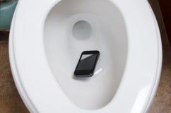 Un teléfono celular en el retrete imágenes de archivo libres de regalías