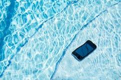 Un teléfono celular que cayó en la piscina fotografía de archivo libre de regalías