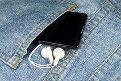 Un teléfono celular y auriculares Foto de archivo libre de regalías