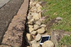 Un teléfono elegante perdió al costado de un camino Imagen de archivo