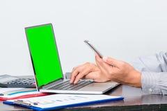 Un teléfono móvil del control del hombre de negocios mientras que comprueba los datos Fotos de archivo