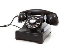 Un teléfono rotatorio retro negro en un fondo blanco Imagen de archivo libre de regalías