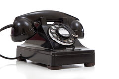 Un teléfono rotatorio negro retro en un fondo blanco Foto de archivo libre de regalías