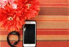 Un teléfono y un reloj con el mantel rojo como fondo Imagenes de archivo