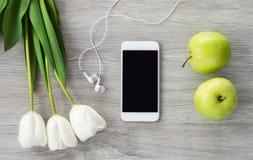 Un telefono bianco con le cuffie bianche, i tulipani bianchi e le bugie verdi delle mele su una tavola di legno bianca fotografia stock