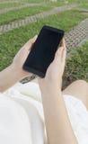 Un telefono femminile della tenuta delle mani fotografia stock