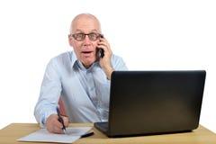 Un teléfono que habla del hombre de negocios y está asombrado Fotos de archivo libres de regalías