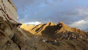 Un templo tibetano con las banderas en la montaña sobre la ciudad metrajes