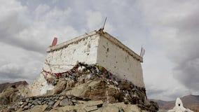 Un templo tibetano en la montaña con las banderas almacen de video