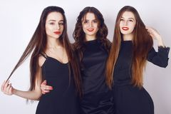 Un tempo pazzo del partito di tre belle donne alla moda in vestito nero casuale da sera elegante che celebrano, divertiresi, ball Fotografia Stock