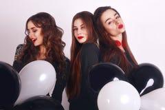 Un tempo pazzo del partito di tre belle donne alla moda in vestito nero casuale da sera elegante che celebrano, divertiresi, ball Immagini Stock