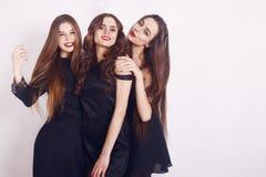 Un tempo pazzo del partito di tre belle donne alla moda in vestito nero casuale da sera elegante che celebrano, divertiresi, ball Fotografie Stock