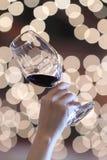 Un tenu dans la main un verre de vin à une partie, fond avec les lumières brouillées Image stock