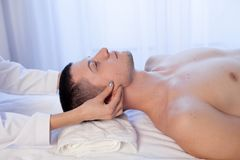 Un terapista di massaggio rende una stazione termale di terapia di massaggio dell'uomo facciale immagine stock