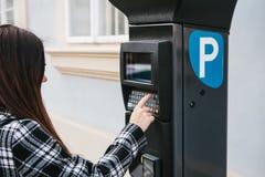 Un terminale moderno per il pagamento il parcheggio dell'automobile Una giovane donna preme un bottone e prova a pagare un parche Immagine Stock