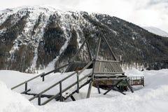 Un terrain de jeu d'enfants sous la neige et les montagnes neigeuses et une petite ville dans les alpes Suisse Images stock