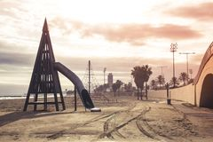 Un terrain de jeu vide d'enfants sur une plage sablonneuse avec des palmiers, o images stock