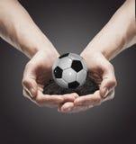 Un terreno di manciata con la sfera di calcio classica nell'uomo Immagine Stock Libera da Diritti