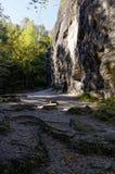 Un terreno roccioso che si trova davanti ad una formazione rocciosa alta Immagine Stock Libera da Diritti