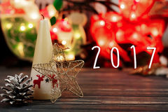 un testo di 2017 segni sulla candela di natale e giocattoli su fondo del luccio Fotografia Stock