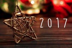 un testo di 2017 segni sulla stella dorata di natale su fondo della ghirlanda Fotografia Stock