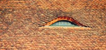 Un tetto di mattonelle e una piccola finestra Immagine Stock