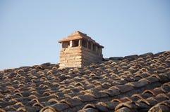 Un tetto piastrellato con un camino fotografia stock libera da diritti