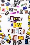 Un texto de la escritura de la palabra que muestra concepto de FELIZ AÑO NUEVO hecha de diversa letra del periódico de la revista foto de archivo