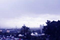 Un throgh della città una finestra piovosa Fotografia Stock