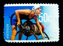Un timbre imprimé dans l'Australie montre une image d'une femme en service pour le club de sauvetage sur la valeur au cent 50 Images libres de droits
