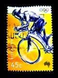Un timbre imprimé dans l'Australie montre une image de cycliste pour le jeu de Jeux Olympiques sur la valeur au cent 45 Photos stock