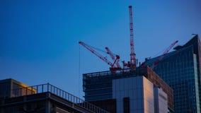 Un timelapse de grúas en la construcción inferior detrás del cielo azul en Tokio almacen de metraje de vídeo