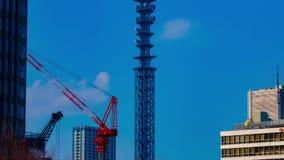 Un timelapse de grúas en la construcción inferior detrás del cielo azul en Tokio metrajes