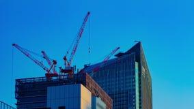 Un timelapse de grúas en la construcción inferior detrás del cielo azul en Tokio almacen de video