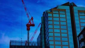 Un timelapse de grúas en la construcción inferior en el edificio en Tokio metrajes
