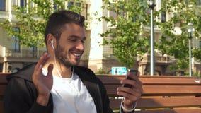 Un tipo allegro risponde ad una video chiamata sul telefono stock footage