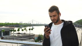Un tipo allegro sta scrivendo qualcosa a macchina in suo telefono archivi video