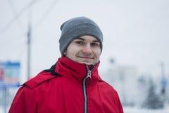 Un tipo bello in un rivestimento rosso ed in un cappello grigio Un giovane tipo con gli occhi verdi Un tipo felice, sorridente ed Fotografia Stock