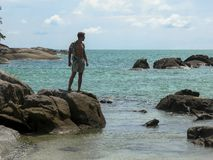 Un tipo bello in una camicia è allungato su una roccia e distoglie lo sguardo Vista esotica del mare Spiaggia selvaggia con le gr fotografie stock libere da diritti