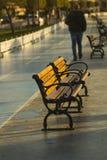 Un tipo cammina a partire da una coppia di banchi di legno della via del ironcast sotto il sole di mattina immagini stock