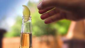Un tipo che mette una calce su una bottiglia di birra video d archivio