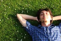 Un tipo che si trova su un campo di erba Fotografia Stock Libera da Diritti