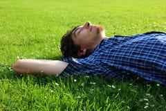 Un tipo che si trova su un campo di erba Fotografia Stock