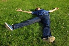 Un tipo che si trova su un campo di erba Fotografie Stock