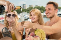 Un tipo con due ragazze beve il champagne su un yacht fotografie stock