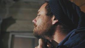 Un tipo con i baffi e barba con i bei occhi azzurri che pettinano la sua barba con un pettine di legno video d archivio