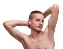 Un tipo con un torso nudo che posa su un bianco ha isolato il fondo Immagine Stock Libera da Diritti