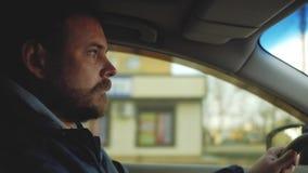 Un tipo con una barba con i bei occhi sta conducendo un'automobile raggi del sole nella finestra stock footage